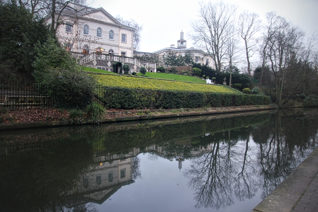 Refections of a mansion and a mosque in a canal