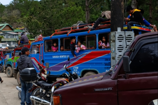 Kids blowing bubbles while playing in a jeepney